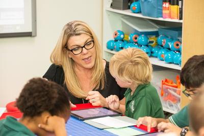 teacher works with kindergarten student on digital portfolio